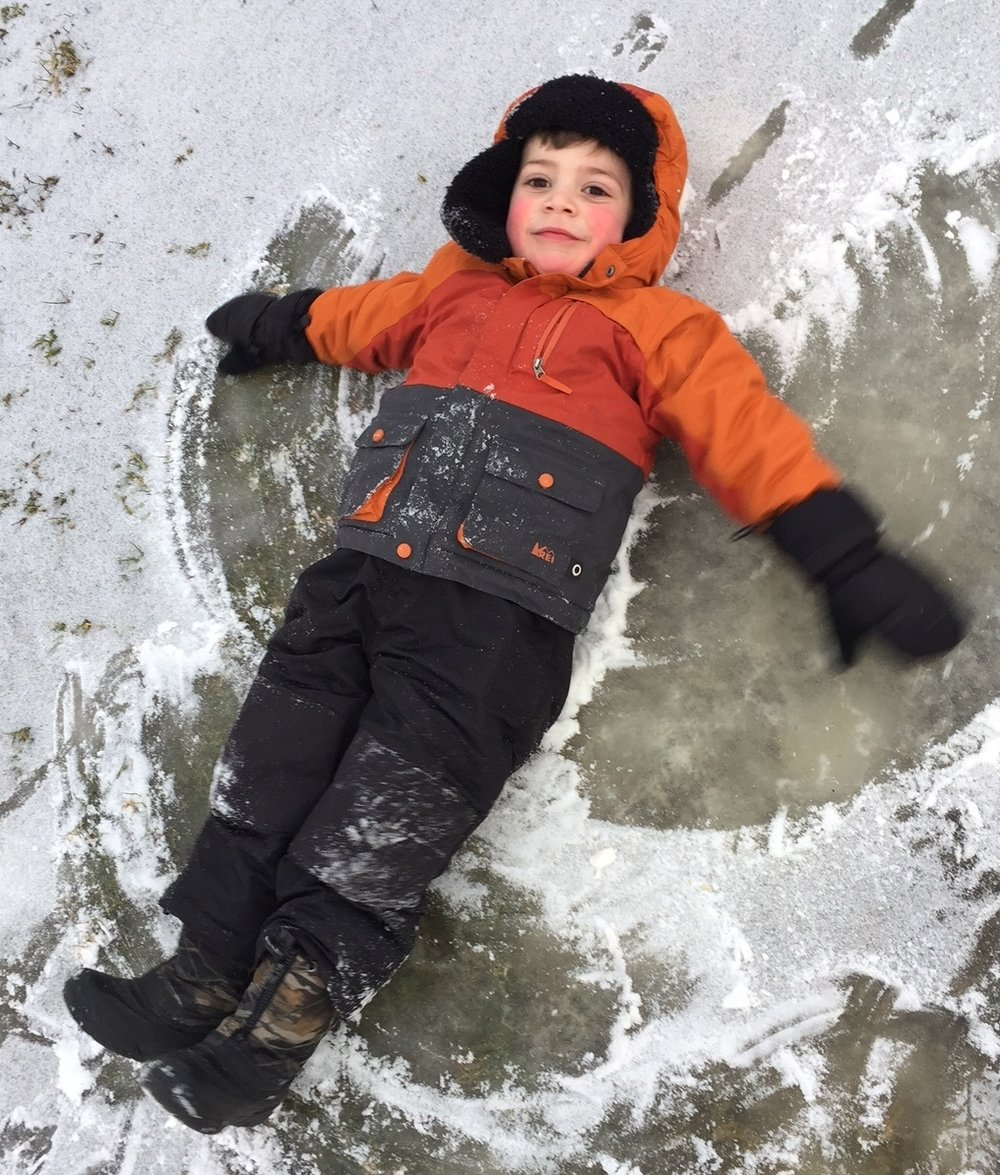 B. learns the art of snow angels!