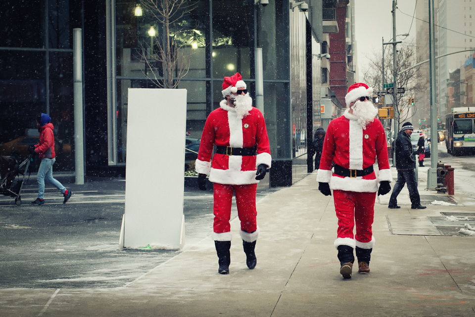 Santa Twins walking down the street during the Santacon event in NYC.