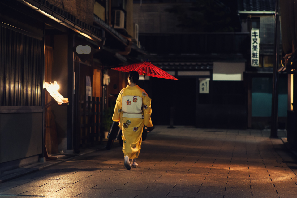 MAIKO WALKING DOWN THE GEISHA DISTRICT IN KYOTO