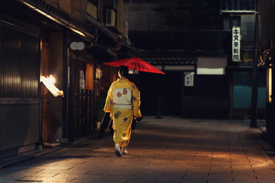 MAIKO WALKING DOWN THE GEISHA DISTRICT IN KYOTO