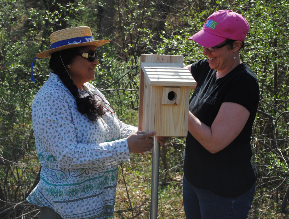 Barbara (left), a conservation easement landowner, and Tracy (right) installing a bluebird box.