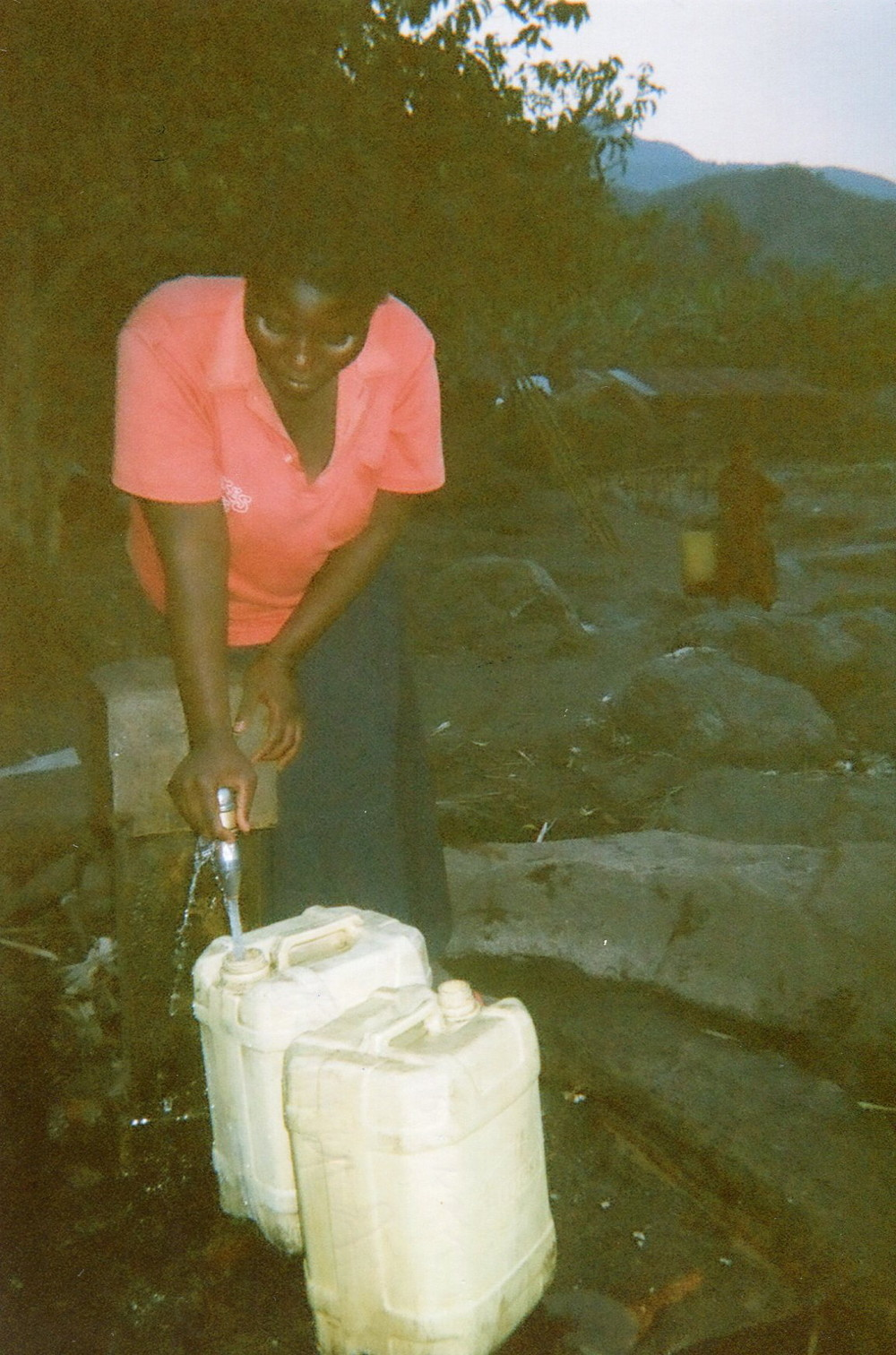 Here I am collecting water from the tap to take to the forest to wash the dishes and for drinking.