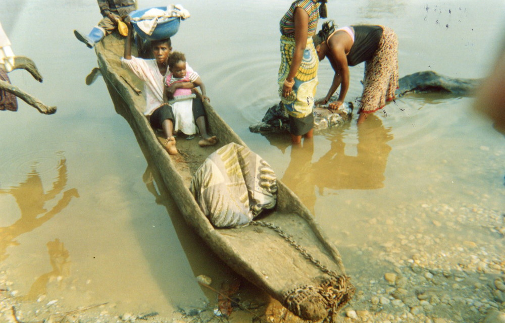Displaced people cross the Elila river in a canoe during the war.