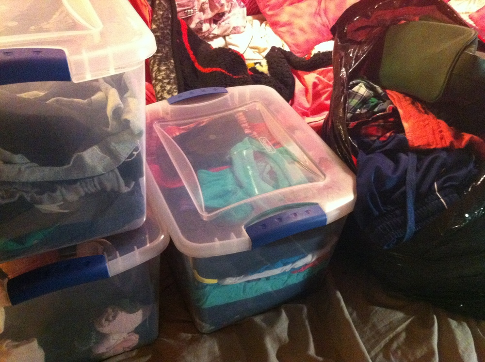 Left: Clear bins for organizing clothes and other items. Right: Bag of clothes and purses to donate.