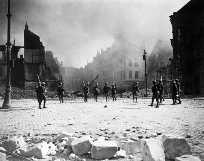 A group of Canadian soldiers strung out in the streets of Cambrai against its still burning buildings. Photo by William Rider-Rider (Imperial War Museum, CO3373)