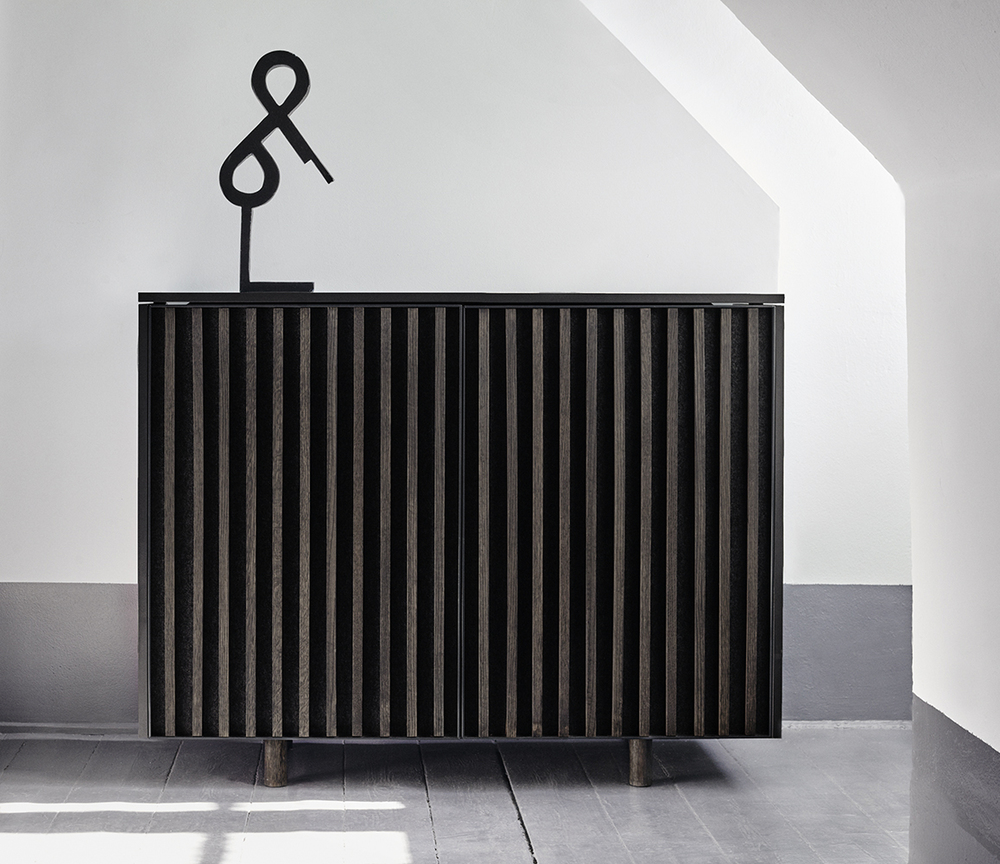 The dB silent cabinet by StokkeAustad features fronts with solid oak slats and thick felt, making the cabinet into a basstrap, absorbing mid- and low frequency noise.
