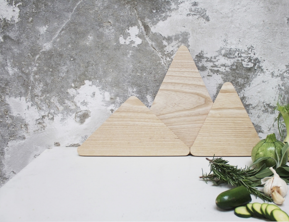 The Mountains is a set of triangular chopping boards designed to resemble a mountain range when stacked together. The Mountains are made from solid ash,  and  contains of three designs, each an isosceles triangle, but with different heights and widths. The combination possibilities are many, so you can vary and create your very own mountain horizon. Designed by Runa Klock for Trefjøla