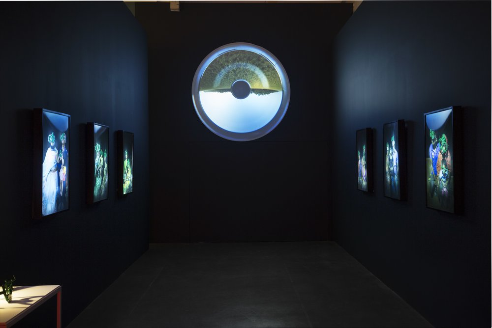 "Firoz Mahmud's ""Soaked Dream"" light boxes + Zihan Karim's Eye from 2014 appearing as an all seing divine being in one of the museum architecture's cul-de-sac""."