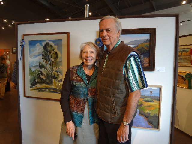 Guest Juror Patti Jacquemain and husband Dave against wall of award winning paintings on display thru Oct. 4th