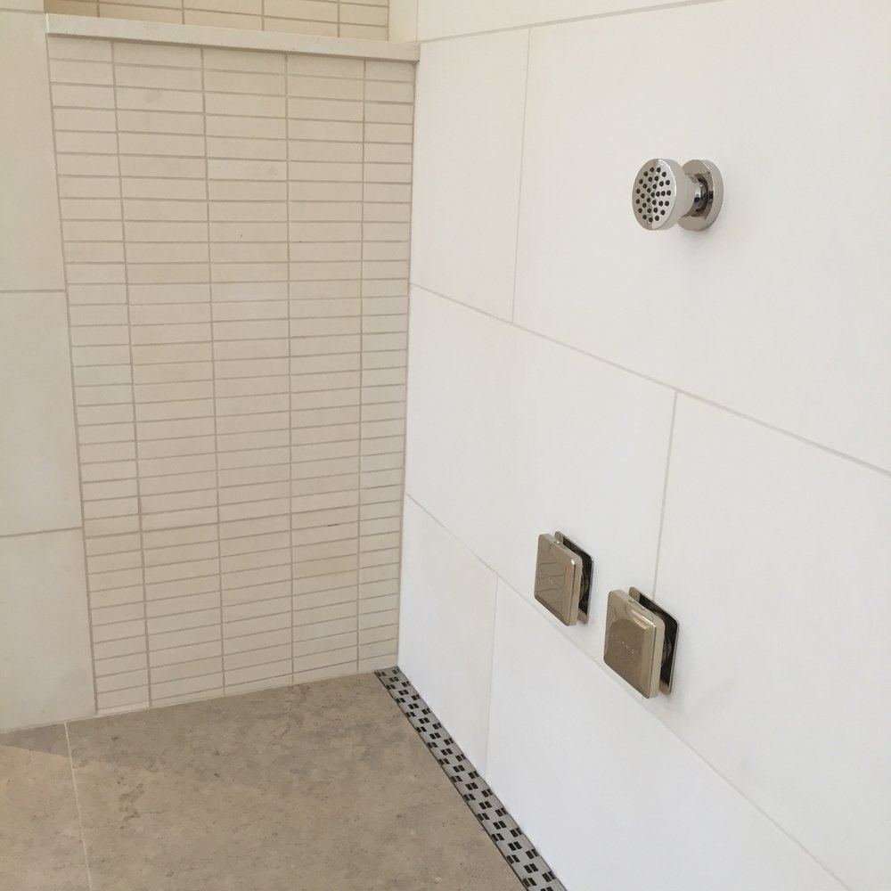 DETAIL:  The shower drain was designed as a linear slot along one entire wall of the large shower.  In this way, we could pitch the entire floor in one direction instead of the typical situation where there is a centrally located drain with the floor pitching in different directions to it.