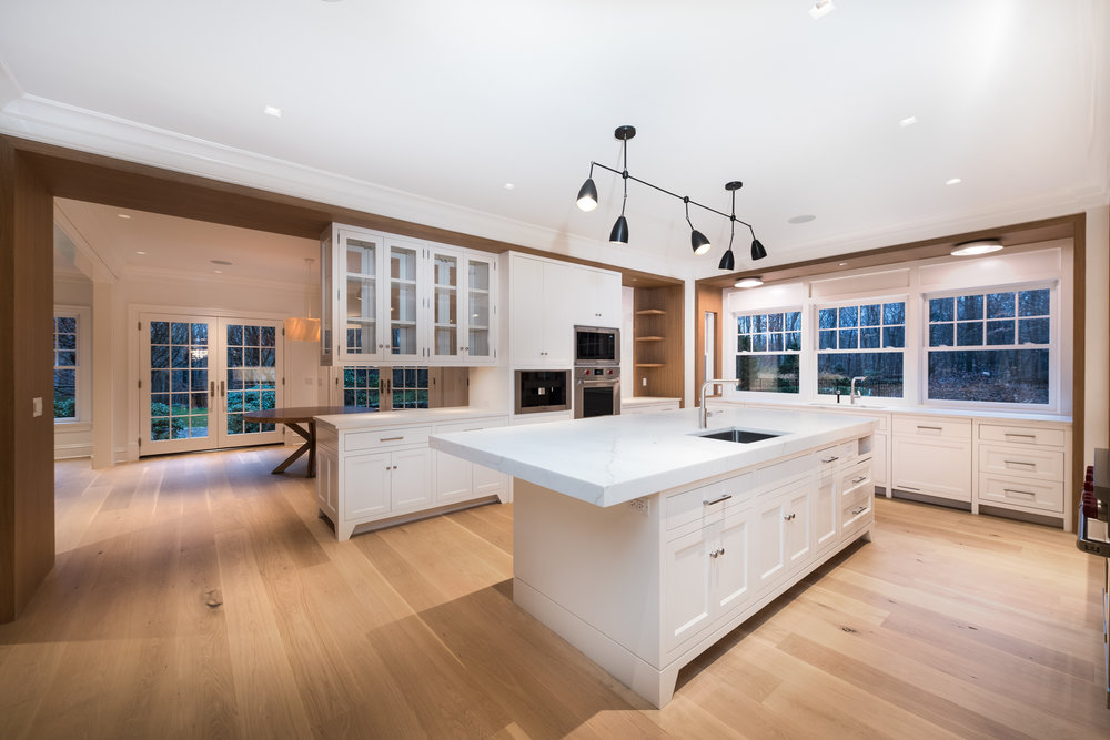 "KITCHEN:  The Kitchen was designed with these white-oak ""frames"" with the painted white cabinetry set into the frames.  These frames are finished to match the adjacent Family Room fireplace and various white oak countertops used throughout the house."