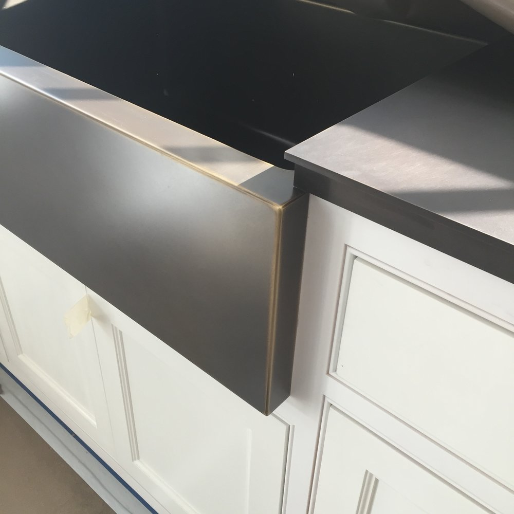 MUDROOM CABINETRY DETAIL:  Here is a custom bronze farmhouse sink we had made from one of our fabricators in Texas along with a custom bronze countertop we had made locally.