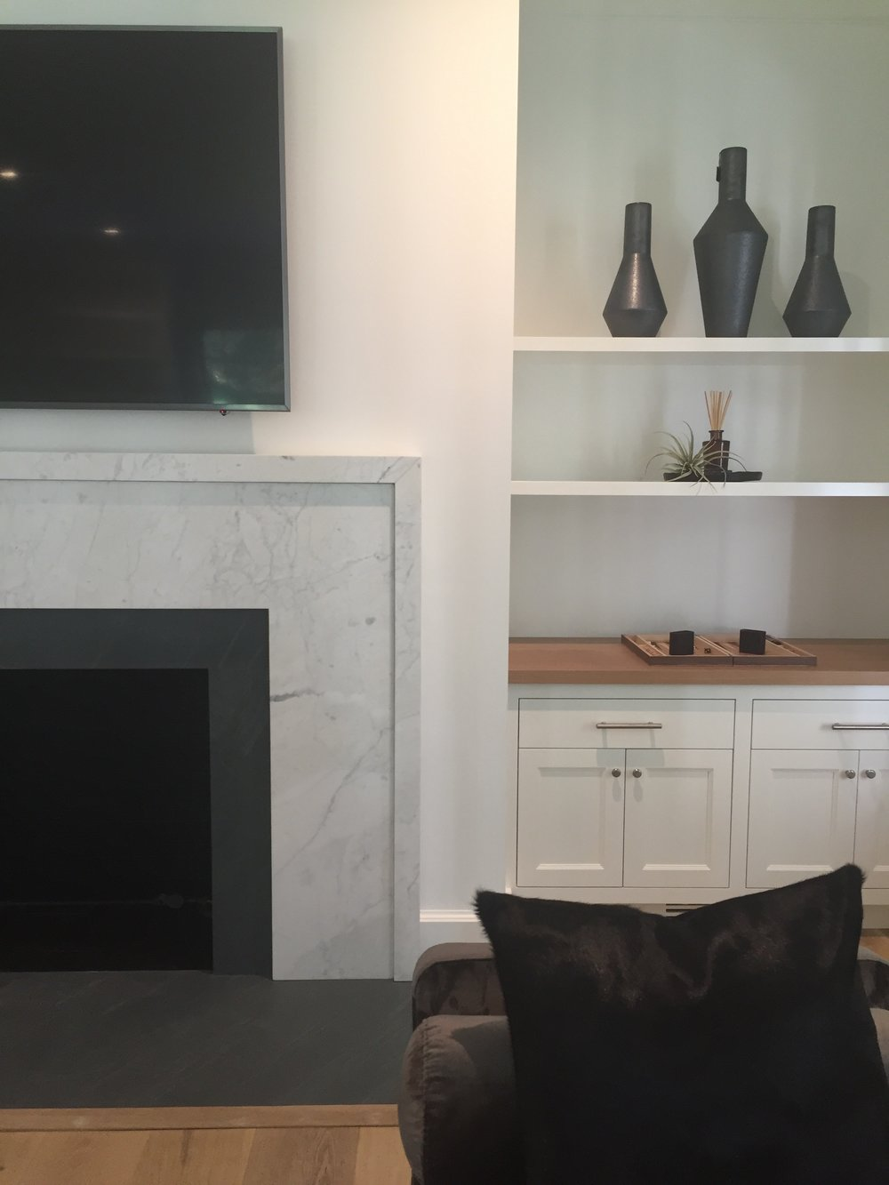 HIS OFFICE (DETAIL):  We ended up gutting an existing dark-wood claustrophobic library and opened it up with clean cabinetry and a simple fireplace surround composed of a dark gray basalt stone and a lighter gray marble surround with a thickened edge detail.