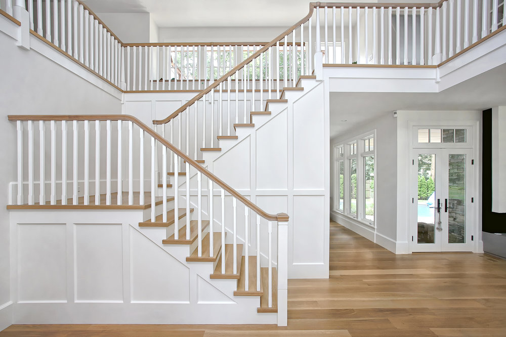 This is the view once you enter the front door.  The Living Room is to the right, the Dining Room is behind the stair, and an open space leading to the Kitchen, Office, Mudroom and secondary stair is to the left.  This central stair is a central figure between all of these spaces.  We panelized the stair and left all other wall treatments as smooth painted surfaces to emphasize the figural quality of the stair as a piece of millwork.  Chunky stair treads and handrails are finished to match the floor in this light filled space.