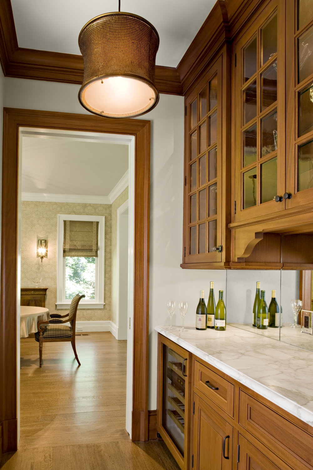 "This is the Butler's Pantry between the Kitchen and Dining Room.  We designed custom mahogany cabinetry and a Calacatta gold counter to match the island in the kitchen.  The backsplash is a lightly antiqued mirror.  In the Dining Room the walls were stenciled by a specialty paint company.  The stencil was sized for the height of the room, so that the baseboard and crown moulding assembly would not cut off the pattern.  This process was a 6 step process to produce the background in a linen finish, and a mix of plaster and paint for the stencil.  The wood flooring is a beautiful rift & quarter sawn white oak in long boards.  In standard construction, wood floors are nailed to formaldehyde emitting underlayment and then finished with solvent-based finishes that will off-gas for months.  In this project, old-fashioned, solid 1x8's were installed diagonally over the framing for the subfloor (instead of plywood), ""dustless"" sanding with a HEPA vacuum was specified to the floor installer and a solvent-free floor finish was used."