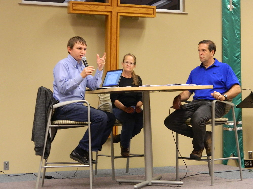 Pastor Rich speaks during the special congregational meeting on Sunday. Listening are secretary Kit Tornberg and vice president Dan Cook.