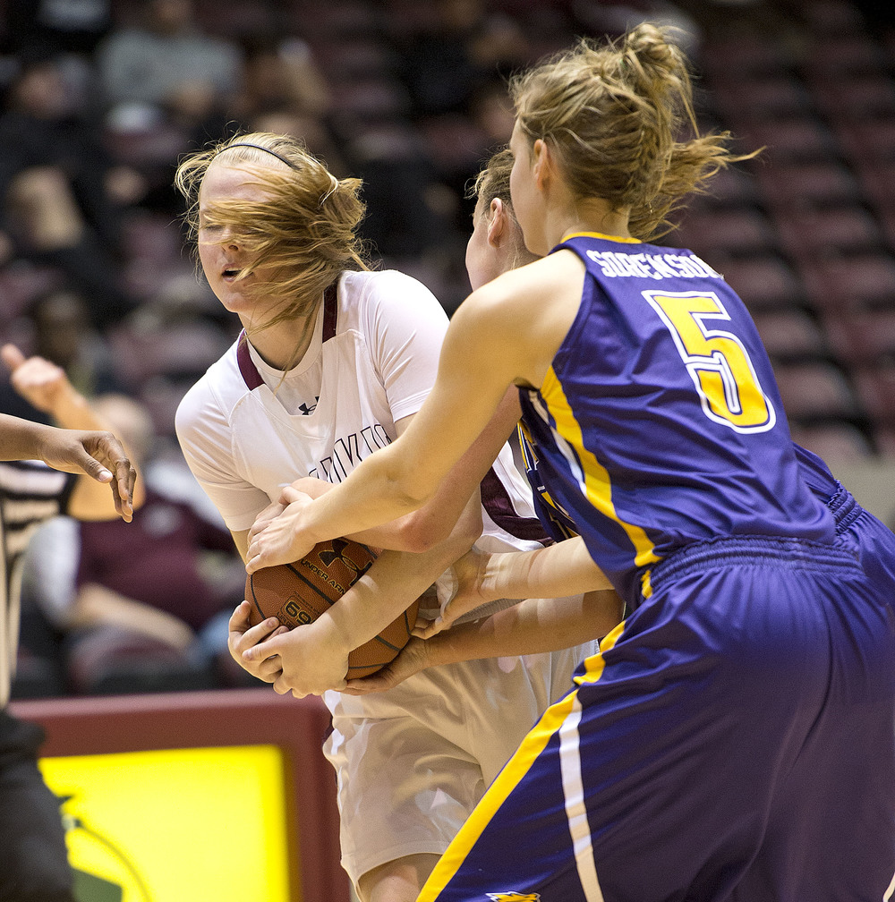 Salukis guard Carlie Corrigan wrestles away the ball while being double teamed by Northern Iowa's Stephanie Davidson and Amber Sorensen.