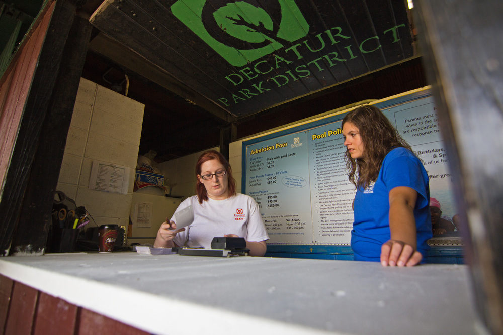 Decatur Park District employees Jessica St. Pierre, left, and Britney Munos go over front desk responsibilities during opening weekend on May 24 at Fairview Pool.