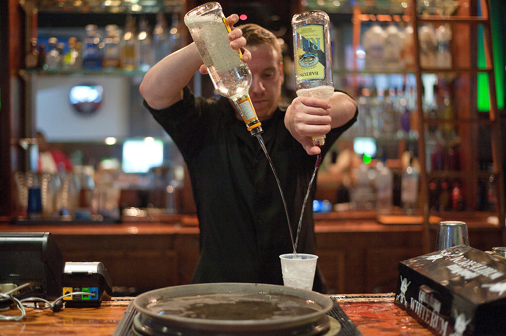 Jon Hall, of Sesser, Ill., mixes a drink on Sept. 20 at Saluki Bar N' Grill in Carbondale, Ill. The bar changed its age limit to 21 and up on Sept. 14.