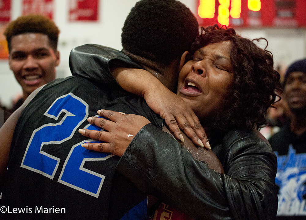 MacArthur's Kamari Jones (22) receives a hug   after the Generals' regional championship game with the Lincoln Railers at Mount Zion High School in Mount Zion, Ill. MacArthur won 57-38.