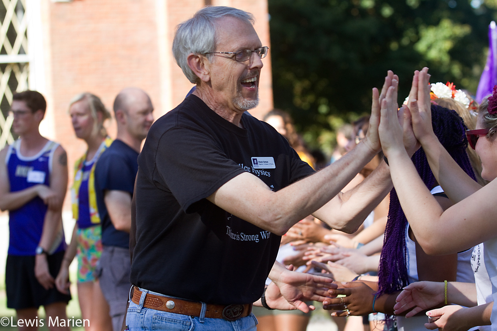 Chuck Schulz, a professor of physics at Knox College, high fives students during Pumphandle at Old Main on the campus of Knox College on Sept. 9.