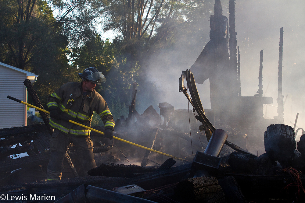 Williamsfield Fire Protection District member Tony Byrd, of Dahinda, Ill., uses a pike pole to clear out debris after the extinguishing of a garage fire at 215 N. Poplar St. in Williamsfield, Ill., on Sept. 16.