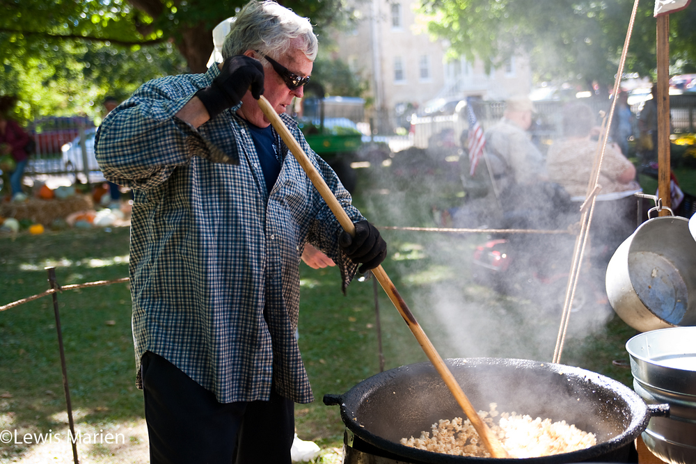 "Dave Snyders, of Alton, Ill., makes popcorn on Sept. 26 during the 44th annual ""Jordbruksdagarna"" (Swedish for ""earth work days"") in Bishop Hill, Ill. Snyders runs Pioneer Karmel Korn, in an attempt to recreate how early pioneers made popcorn, by mixing oil and sugar in an iron kettle."
