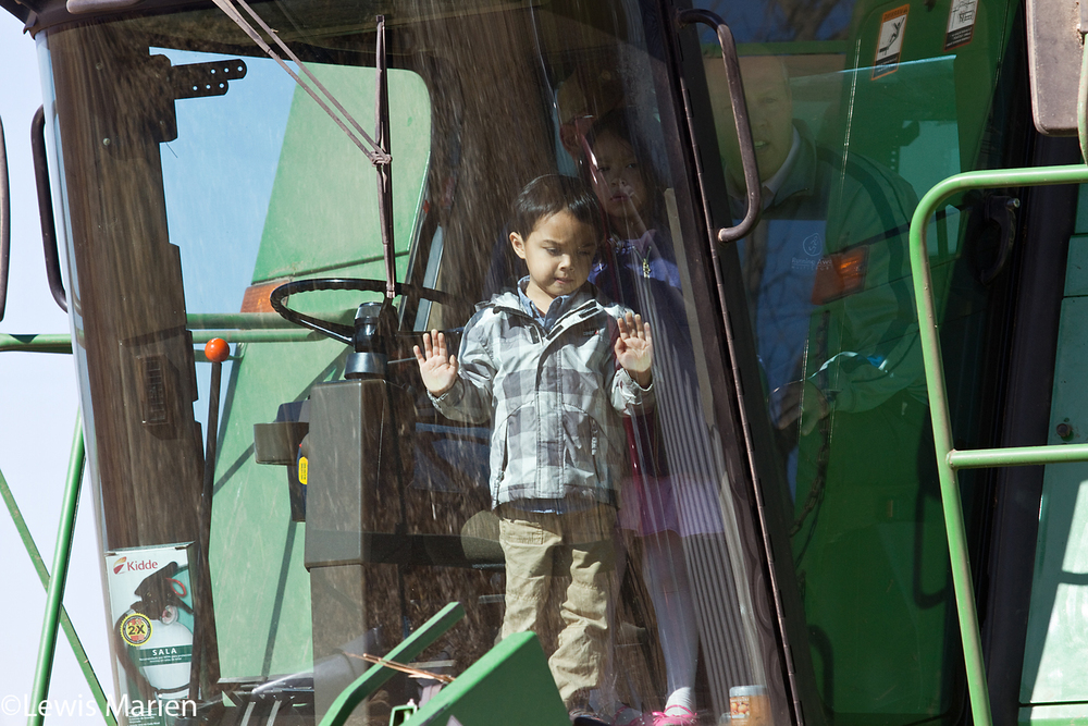 Luke Sanburg, 4, of Rolling Meadows, Ill., looks out the window while on a combine ride Sunday with his sister Julia, 5, and their father Paul during the 10th annual Twin Rivers: Harvest of Hope Foods Resource Bank Harvest Celebration on Oct. 18 at Nelson Farm near Galesburg, Ill.