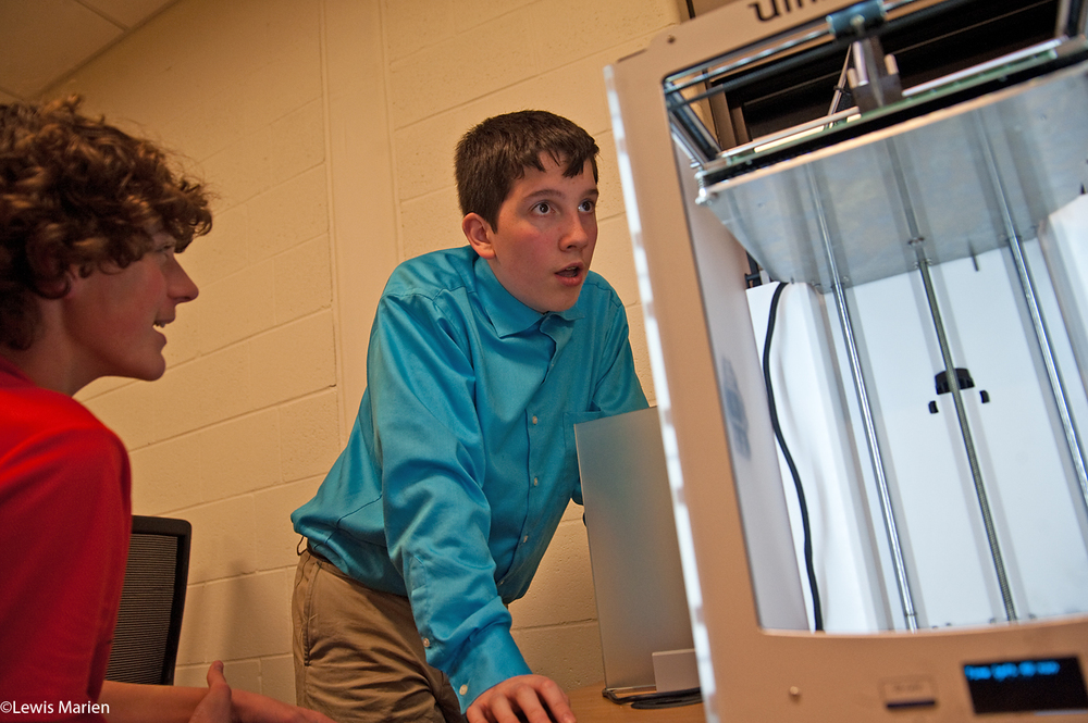 Knoxville High School freshmen Jacob Betz, left, and Steven Comandini watch a 3-D printer in action on Nov. 23. The high school in Knoxville, Ill., recently added two 3-D printers and started a robotics team.