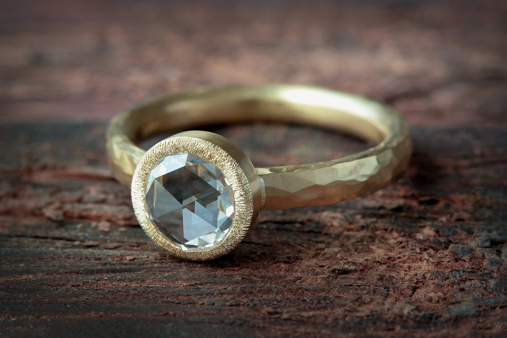 Crafted around a distinctive antique-inspired rose cut diamond, this custom 18k yellow gold engagement ring was completely hand forged and hand finished in our workshop by our expert goldsmith. 00453