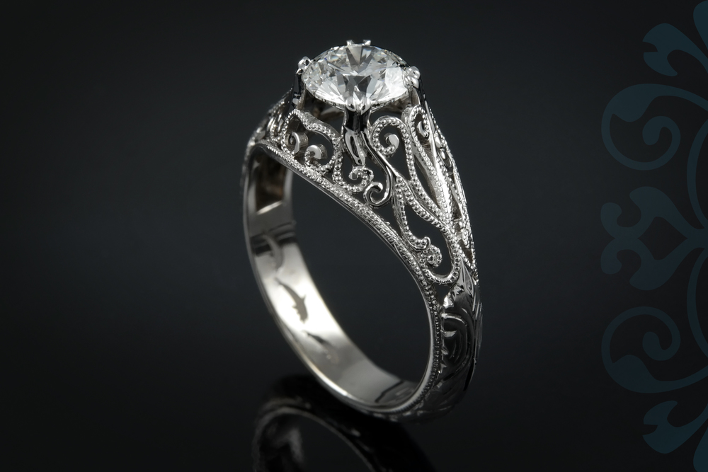 This round diamond seems to float atop the fine milgrain filigree of this 14k white gold engagement ring. 00896