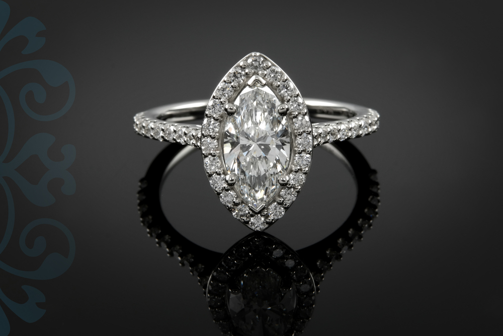 The light halo, feminine diamond accented shank, and simplicity of this engagement ring help emphasize the bold marquise shape of the diamond. 01071