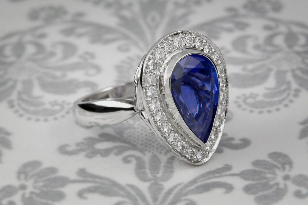 Jewelry restyle inspiration struck one of our dear clients and we helped her transform her 7.06 ct. pear shape Tanzanite gemstone and diamonds from a pendant into a distinctive Platinum ring with 24 accent diamonds. 01122