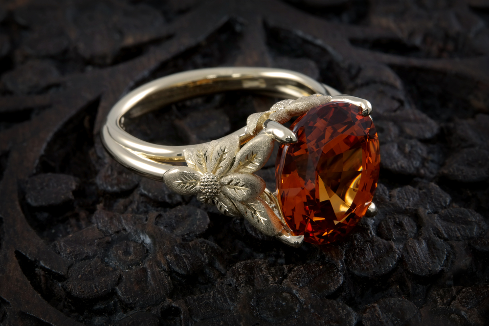 This vibrant, amber 7.27 carat Oval Spessartite Garnet sits in a nature-inspired floral 18K yellow gold mounting with hand finished textures and accents. 00875