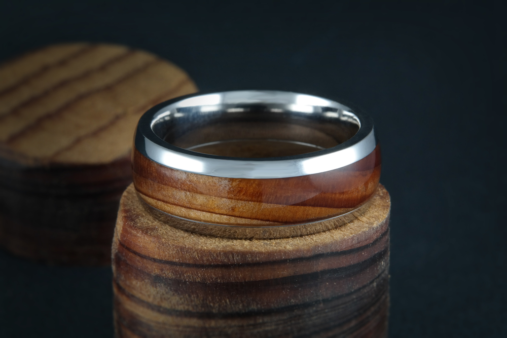 The origin of this custom crafted wedding band goes back over 300 years! The owner had a piece of a Peggy Cypress tree over 300 years old that was reclaimed from a river in Southern Louisiana with sentimental meaning. That wood was inlaid and crafted into this unique and special ring. 00638