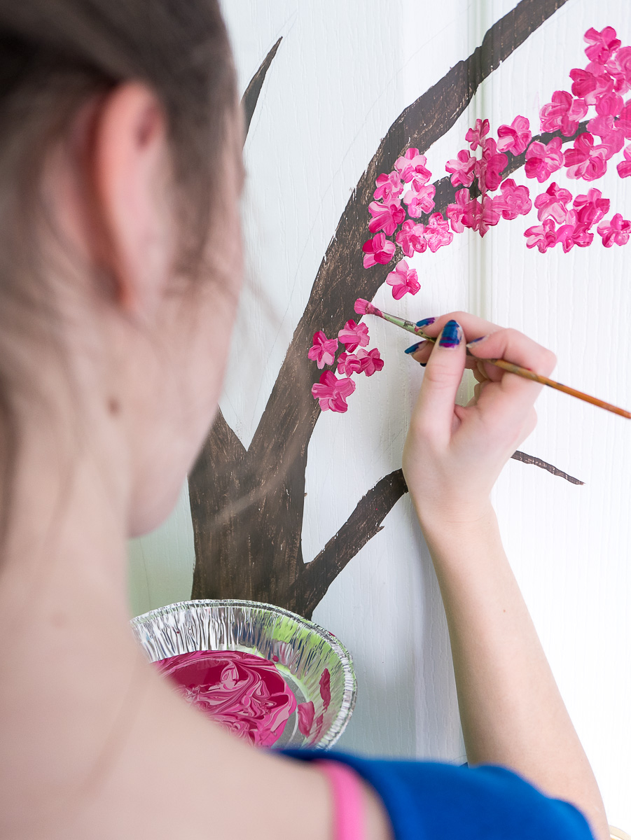 Sarah painting a cherry tree on her bedroom door