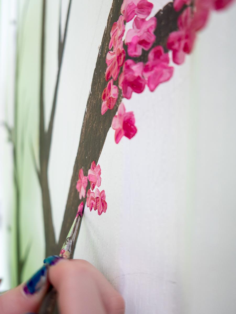 Sarah painting a cherry tree on her bedroom door