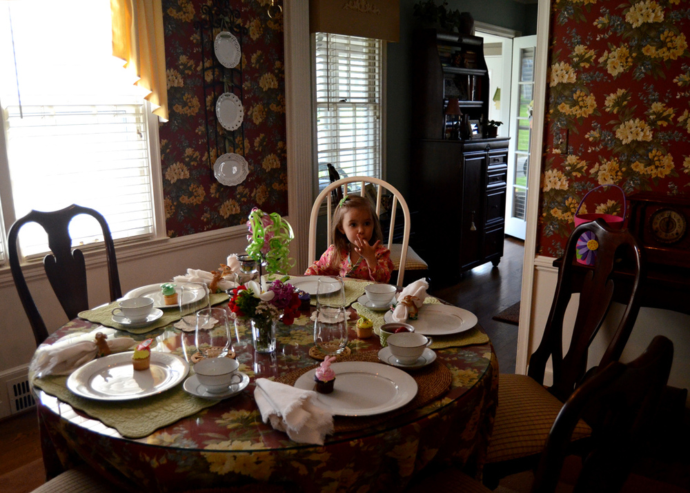 Sampling her cupcake frosting while waiting on the adults for Easter breakfast