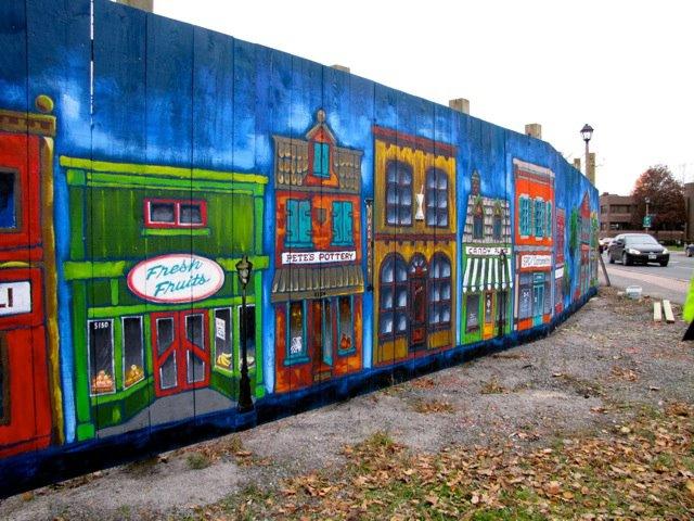 Artists create beautiful mural around construction site for Construction site wall mural