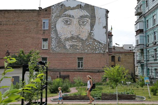 A portrait of slain Maidan activist Serhiy Nihoyan decorates the wall in Heavenly Hundred Garden, planted by activists on Mykhailivska Street.   © Anastasia Vlasova From  Kyiv Post