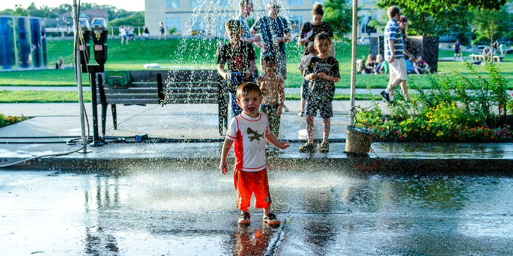 Day 2 was almost too hot to handle, here some children cool off in the sprinklers.