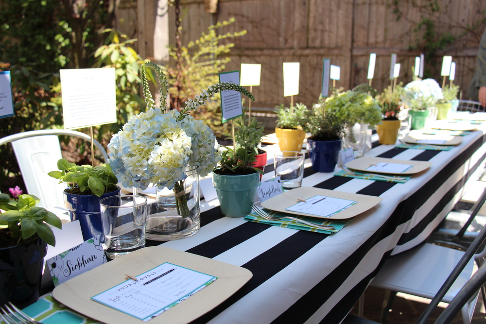 Let a bold pattern to do the heavy lifting.     With the seated lunch happening in my Brooklyn backyard,  the dining table became the main focus for all the decor. For our Alice in Wonderland Garden Party look & feel, I used 5 yards of  black and white fabric from IKEA  to ground our table scape. The fabric was dramatic, fun and affordable!   It also camouflaged my mismatched tables that were different widths and lengths!