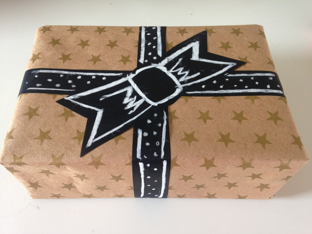 I'm always scrambling around my house to find gift wrapping materials in decent shape, and rarely do I have cute ribbon on hand. Chalkboard tape saves the day! I wrapped this gift with leftover christmas paper and cut out a ribbon and bow to apply to the box. Then I scribbled a quick design to make it look intentional .