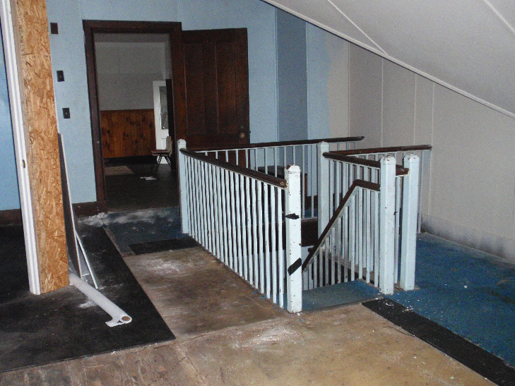 Stairs leading from the upstairs office area to the men's locker rooms.
