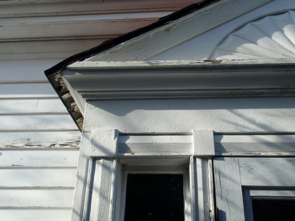 A detail of the entry which shows the blind carved fanlight over the door, often found on Federal style houses, and the simple cornerblocks, hallmarks of the Greek Revival style.