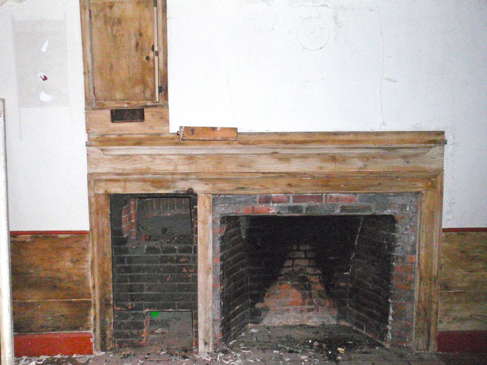 The fireplace in the historic kitchen has a bake oven to the left. The mantel, while original, has unfortunately been stripped of paint.