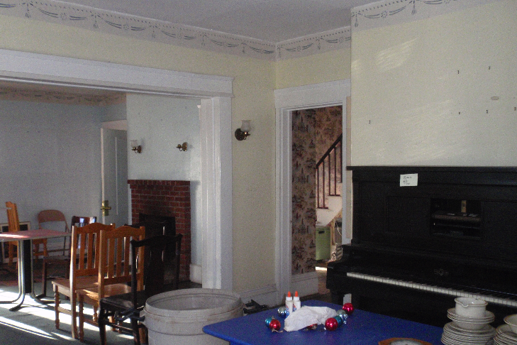The wall between the two front rooms was removed at some point, to open the space up. The fireplace in the rear room has been removed, while the one in the front room has a modern brick surround.