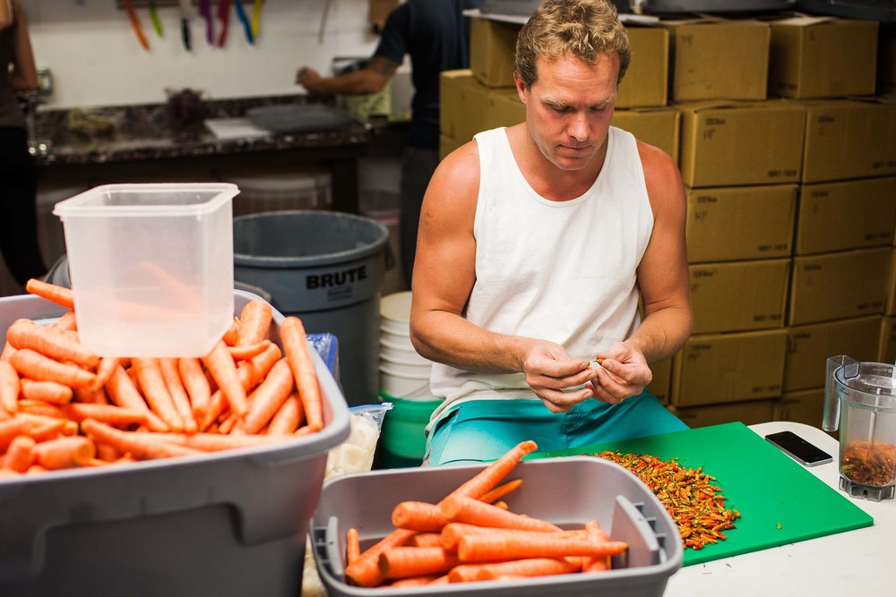 Owner Dylan Veighl sorting peppers for their specialty hot sauce.