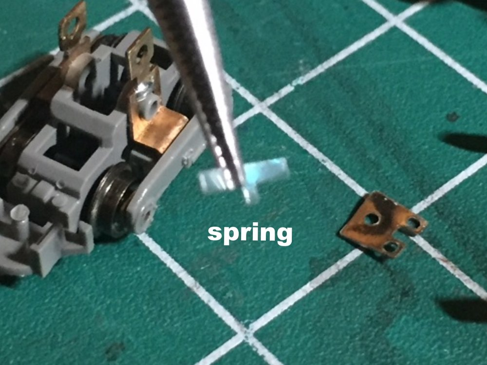 Step 8 - 1. Use tweezers to remove the clear plastic coupler spring.Note: The spring is difficult to see. It sits flat against the back wall of the coupler box.