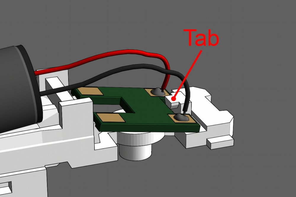 Step 7 - Set the circuit board on the frame and slide it under the tab. Place it with the same orientation as seen in the image.